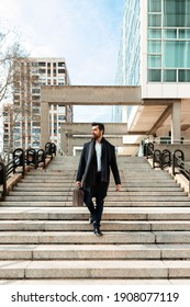 young businessman walking down a flight of stairs after a meeting