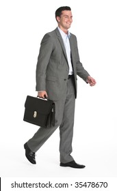 A young businessman is walking and holding a briefcase.  He is smiling and looking away from the camera.  Vertically framed shot.