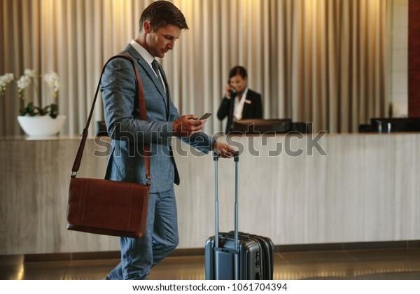 Junge Geschäftsleute, die in der Hotellobby spazieren und mit dem Handy telefonieren. Geschäftsreisender kommt in seinem Hotel an.