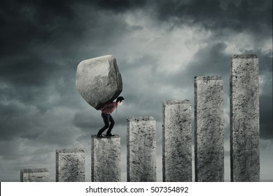 Young businessman walking on the financial chart while carrying a big stone. Concept of hard work