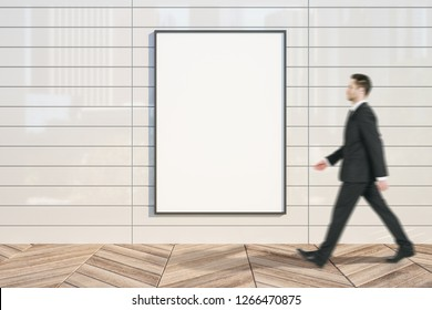 Young businessman walking past empty banner on white tile wall with city reflections. Mock up,
