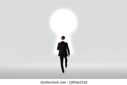 Young businessman walking towards light from keyhole