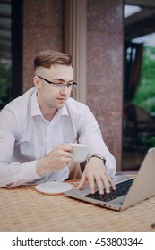 young businessman walks through the city, drinking coffee in a cafe and engaged in work