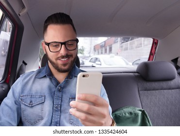 Young businessman wearing denim shirt using his smart phone while on his commute to work in private vehicle transportation. Concept of city life, journey, motivation, transport service.