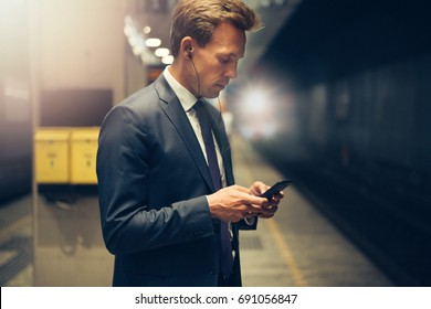 Young businessman wearing earphones and reading text messages on his cellphone while standing on a subway platform during his morning commute