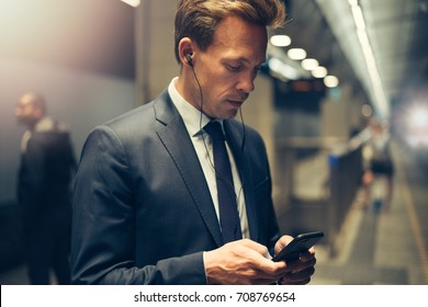 Young businessman wearing earphones and sending text messages on his cellphone while standing on a subway platform during his morning commute