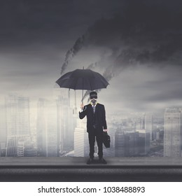 Young businessman wearing a gas mask and holding an umbrella while standing on the rooftop with polluted city background