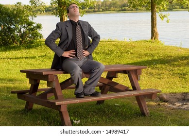 A young businessman wearing a grey suit doing deep breathing exercises