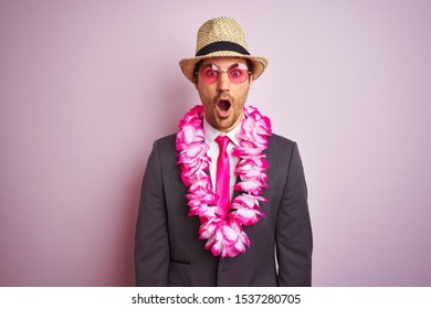 Young businessman wearing suit hat glasses hawaiian lei over isolated pink background scared in shock with a surprise face, afraid and excited with fear expression