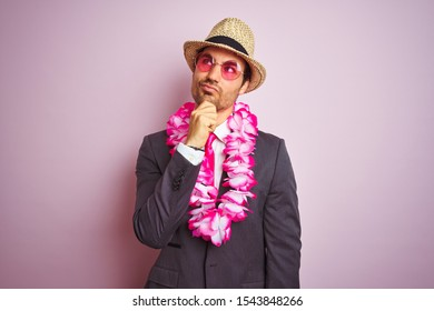 Young businessman wearing suit hat glasses hawaiian lei over isolated pink background serious face thinking about question, very confused idea