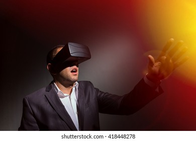 young businessman wearing virtual reality glasses and playing a simulation with amazament