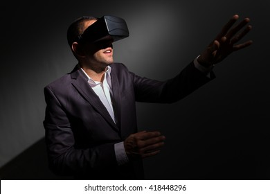 Young businessman wearing virtual reality glasses and doing gestures