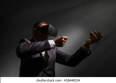young businessman wearing virtual reality glasses and pointing with a virtual shotgun