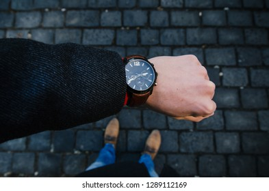 Young businessman wearing watch with coat. Winter in the city. Lifestyle photo. Urban scene in the Prague.