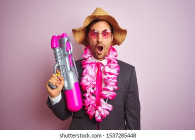 Young businessman wearing water gun hawaiian lei hat glasses over isolated pink background scared in shock with a surprise face, afraid and excited with fear expression