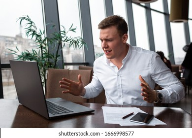 Young businessman wearing a white fashion shirt praying and waiting for success in business in a cafe with a laptop, phone, documents and pen. Freelance and selfemployment concept. Distance job
