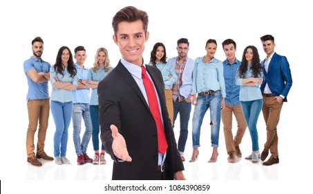 young businessman welcomes you to his casual team with a handshake while standing on white background