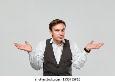 Young businessman in a white shirt and grey vest is at lost shrugging his shoulders isolated over grey background.