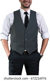 A young businessman in a white shirt with rolled up sleeves stands and keeps his hands in the pockets of his trousers. Hipster guy in a stylish gray waistcoat