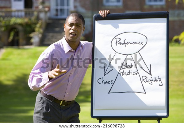 Young businessman with whiteboard outdoors