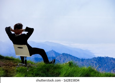 Young businessman who sits on a chair at the top of the mountain and looks into the sky