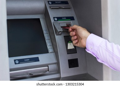 Young businessman withdrawing money from a cash machine