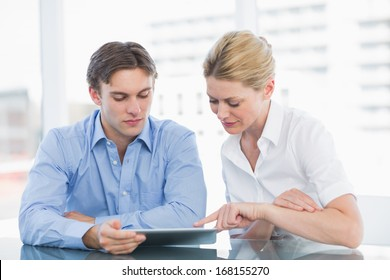 Young businessman and woman using digital tablet at a bright office