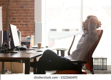 Young businessman worker taking break at work relaxing sitting in ergonomic chair at office desk resting finished computer work found solution holding hands behind head satisfied with job well done