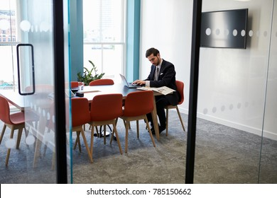 Young businessman working alone in a boardroom