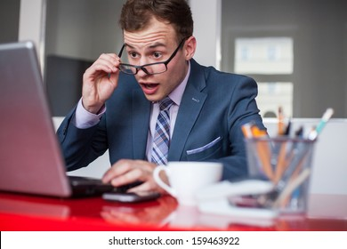 Young businessman working in bright office, sitting at desk with laptop. Expression of emotions.