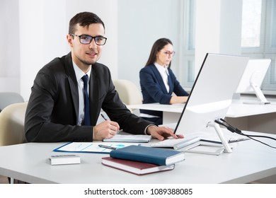 Young businessman working with computer in an office and looks at the camera