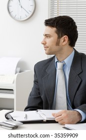 Young businessman working at desk at office.