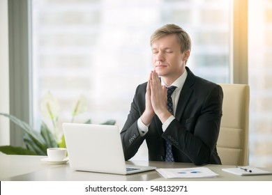 Young businessman working at desk in yoga pose, praying, meditating, relaxing. Stress free work, time for practice, mindfulness and wellbeing, stay healthy on physical, mental emotional level concept
