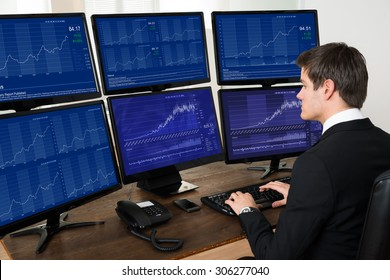 Young Businessman Working With Graphs On Six Computers At Desk