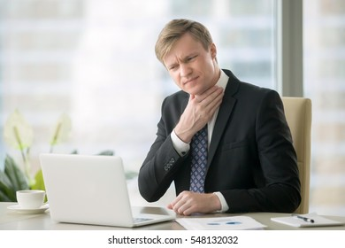 Young businessman working with laptop at desk in the office, hand at his neck, feeling unwell, have a sore throat, after loud screaming, loss of voice, irritation, pain, and itchiness, hard to swallow