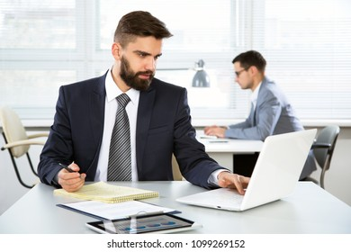 Young businessman working with laptop in an office