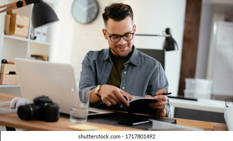 Young businessman working with laptop at office. Businessman sitting at office desk working on laptop computer.