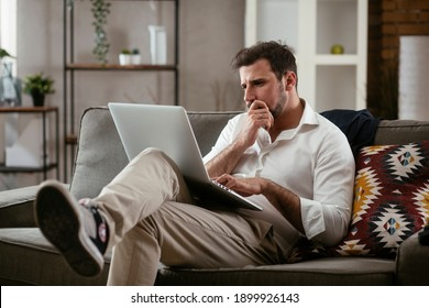 Young businessman working with laptop at office. Businessman sitting on sofa having video call