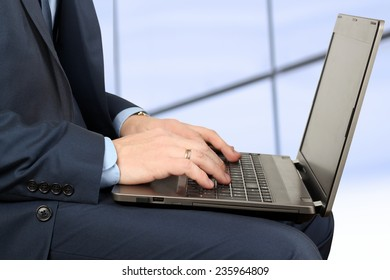 young businessman working  with  a laptop,  sitting inside
