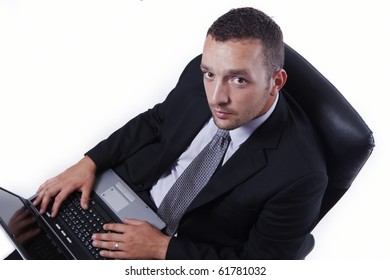 Young businessman working with laptop and sitting at office chair, isolated on white, wearing dark suit