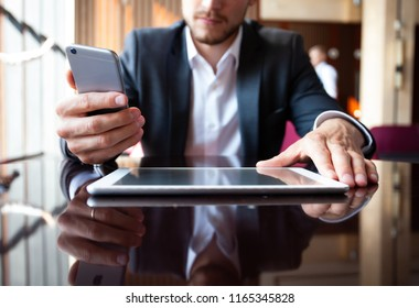 Young businessman working with modern devices, digital tablet computer and mobile phone. New technologies for success workflow concept