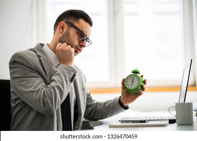 Young businessman is working in office. He is running late on schedule.