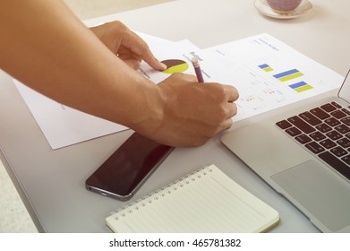 Young businessman working in the office with laptop,phone,notepad.