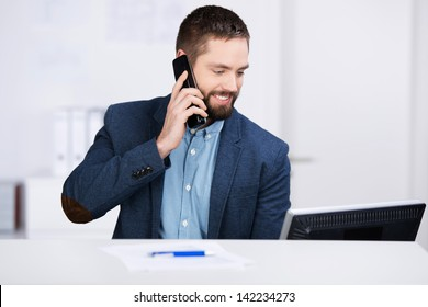 Young businessman working on computer while using mobile phone at desk in office