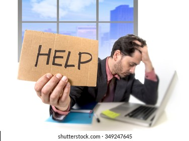 young businessman working on computer laptop asking for help holding cardboard sign looking desperate and depressed in stress overwhelmed and overwork at business district office