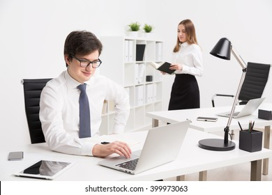 Young businessman working on computer, office table. Young businesswoman with book at background. Concept of office work.