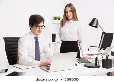 Young businessman working on computer, office table. Young businesswoman standing next to him. Concept of office work.