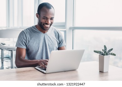 Young businessman working on his laptop in spacious bright office.
