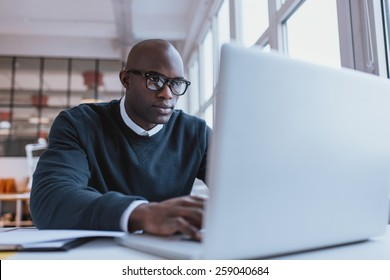 Young businessman working on his laptop in office. Young african executive sitting at his desk surfing internet on laptop computer.