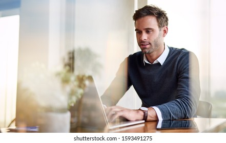 Young businessman working on a laptop while sitting at a dining table at home